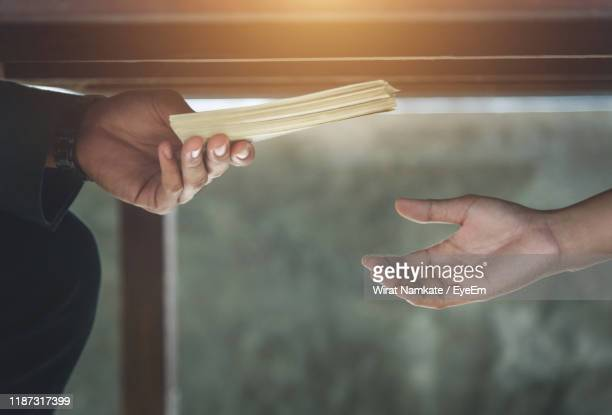 cropped hands of businesswoman giving bribe to man under table - corruption stock pictures, royalty-free photos & images