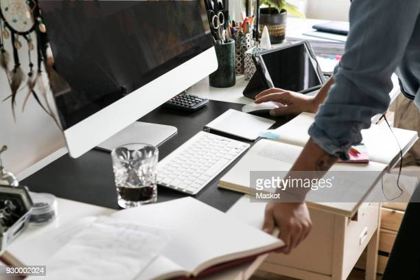 Cropped hands of businesswoman using computer at home