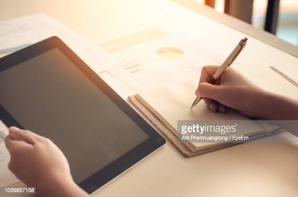 cropped hands of businesswoman writing on book at desk - 大人のみ ストックフォトと画像