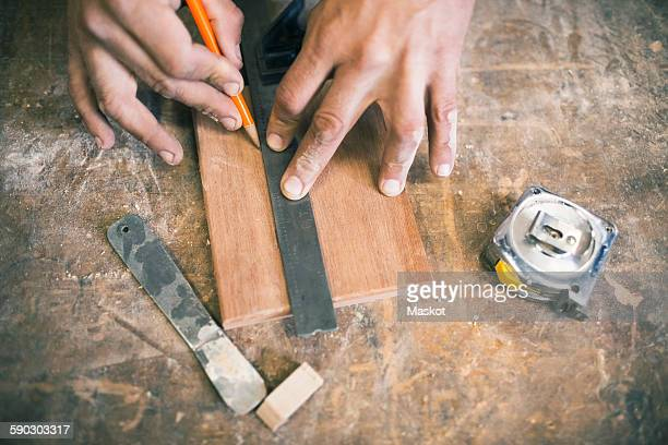 Cropped hands of carpenter marking with pencil on wooden plank at workshop