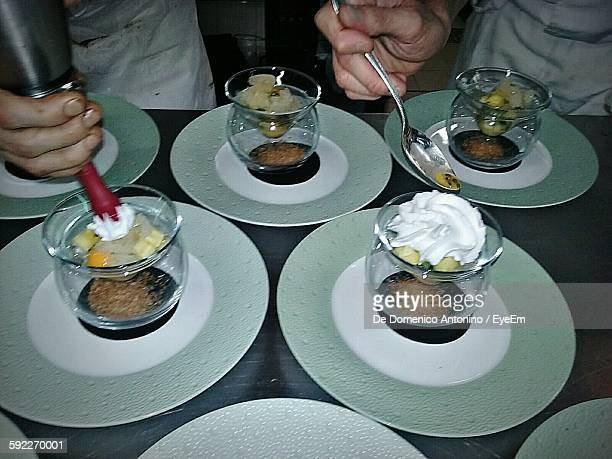 Cropped Hands Of Chefs Preparing Desserts In Plate On Table
