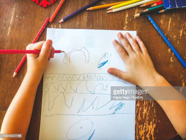 cropped hands of child drawing on paper at table - ingrid held photos et images de collection