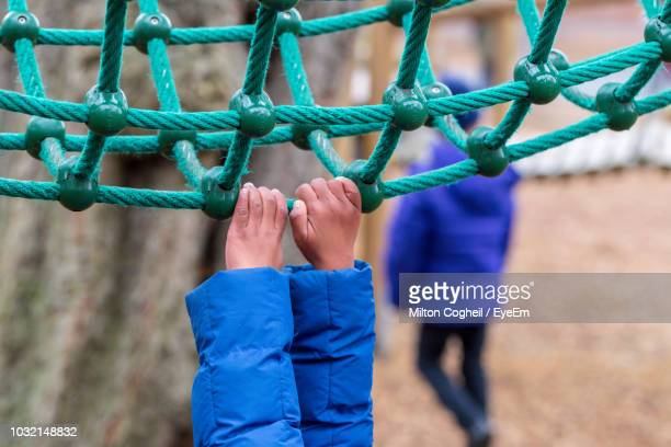 cropped hands of child holding rope while playing at playground - ジャングルジム ストックフォトと画像