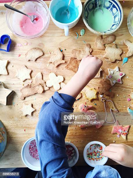 cropped hands of child making cookies at table - accompagnement photos et images de collection