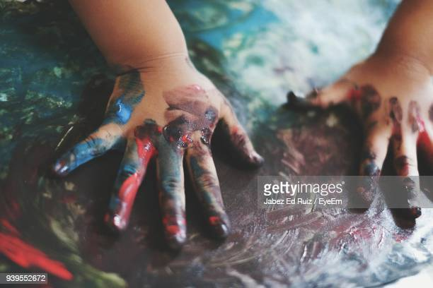 Cropped Hands Of Child Making Painting