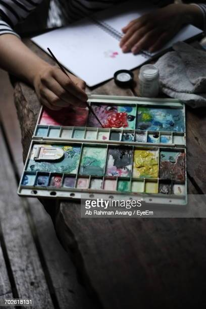 cropped hands of child painting at wooden table - paleta de cores imagens e fotografias de stock