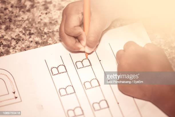 cropped hands of child writing on book at table - lettera b foto e immagini stock