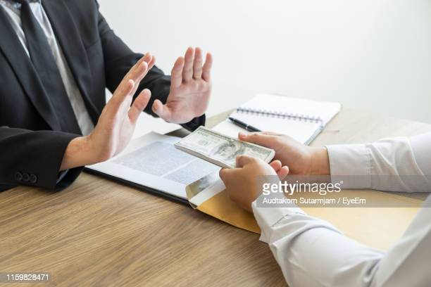 cropped hands of client giving bribe to businessman at office - afwijzing stockfoto's en -beelden