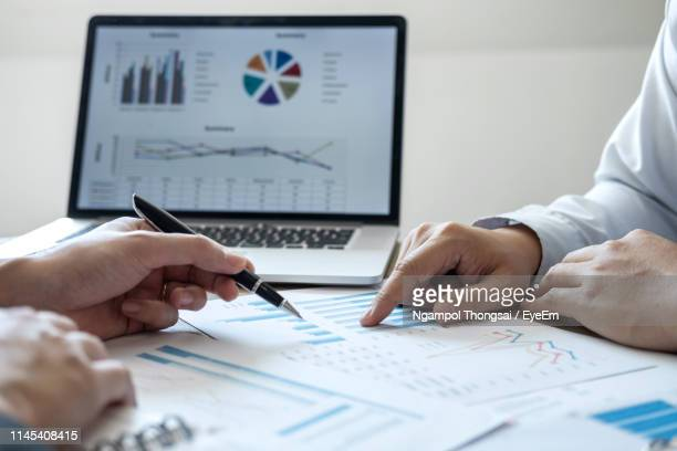 Cropped Hands Of Colleagues Discussing Data On Desk In Office