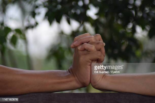 Cropped Hands Of Couple Against Trees