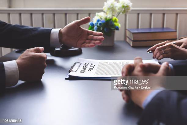 Cropped Hands Of Couple By Lawyer With Divorce Paper On Desk