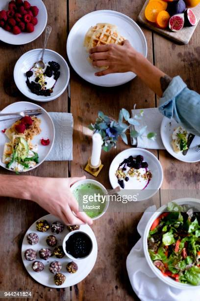 cropped hands of couple having food at table while sitting by wall - the brunch stock pictures, royalty-free photos & images