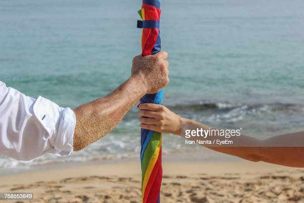 Cropped Hands Of Couple Holding Colorful Umbrella At Beach