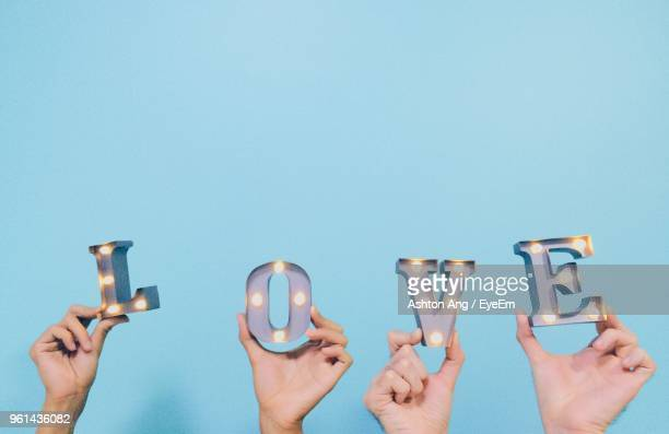 Cropped Hands Of Couple Holding Love Text Against Blue Background