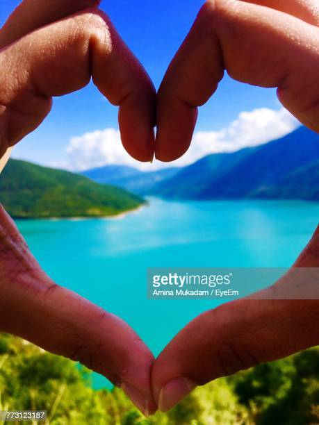 Cropped Hands Of Couple Making Heart Shape Against Lake