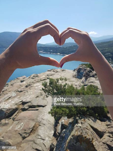 Cropped Hands Of Couple Making Heart Shape By Mountains Against Sky