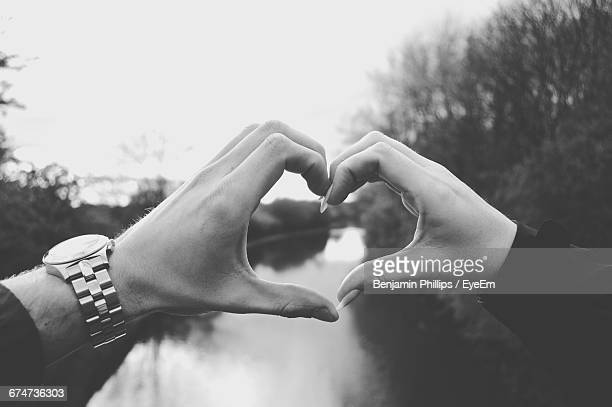 Cropped Hands Of Couple Making Heart Shape Over River