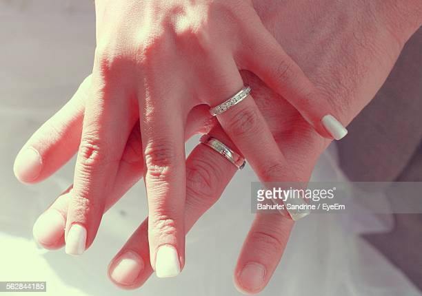 Cropped Hands Of Couple With Wedding Rings