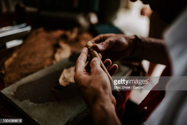 cropped hands of craftsperson making cigar leaves at workshop - cuban culture stock pictures, royalty-free photos & images