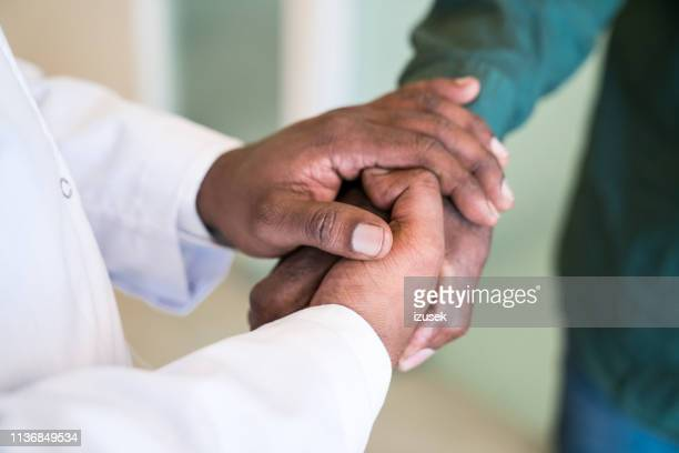 cropped hands of doctor greeting senior man - hand shaking hands stock pictures, royalty-free photos & images