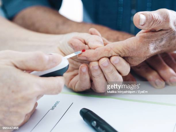 Cropped Hands Of Doctor Testing Blood Sugar Of Patient In Hospital