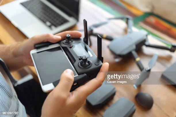 cropped hands of engineer using mobile phone with remote control in office - remote control helicopter stock photos and pictures