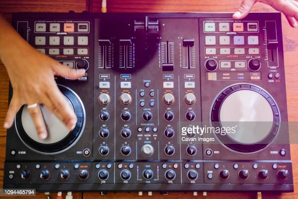 cropped hands of female dj mixing sound on table in recording studio - 電子音楽 ストックフォトと画像