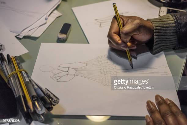 cropped hands of female fashion designer drawing on paper at desk - pencil drawing stock pictures, royalty-free photos & images