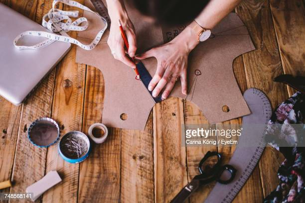 Cropped Hands Of Female Fashion Designer Working On Wooden Table At Studio