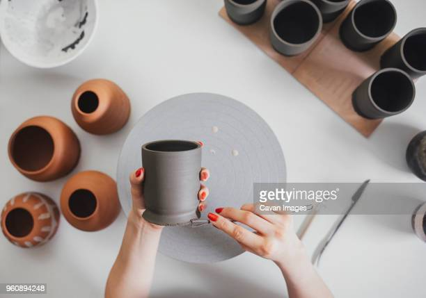 cropped hands of female potter making ceramics at table in workshop - ceramics stock pictures, royalty-free photos & images