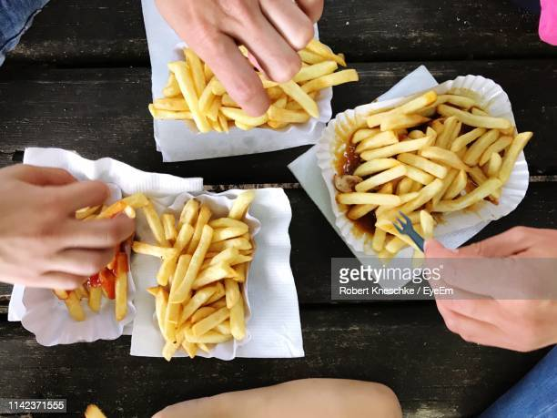 cropped hands of friends eating french fries on table - french fries stock pictures, royalty-free photos & images