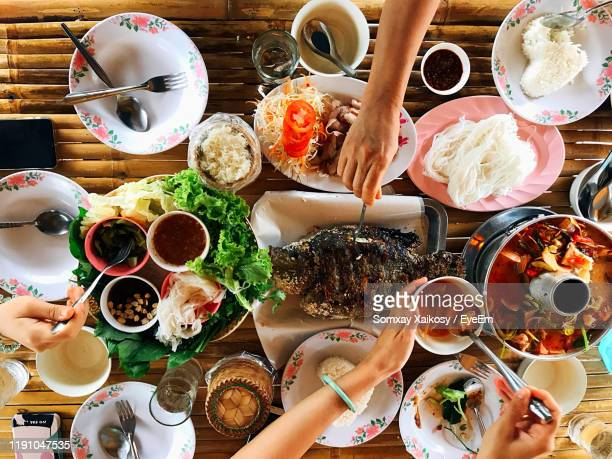 cropped hands of friends having food on table - thai food stock pictures, royalty-free photos & images