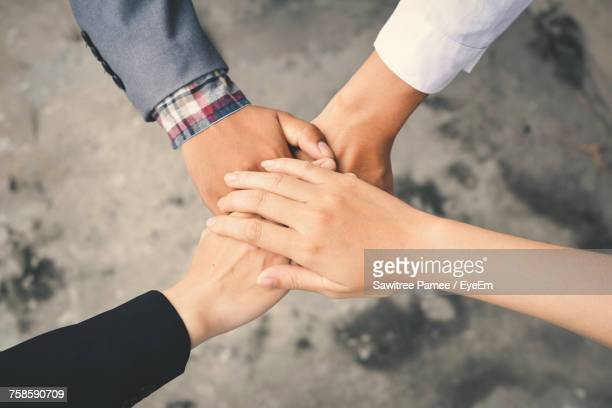cropped hands of friends making oath pile on sidewalk - quattro persone foto e immagini stock