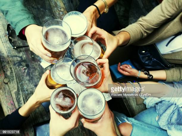 Cropped Hands Of Friends Toasting Alcoholic Drinks