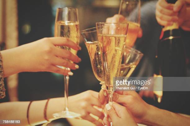 Cropped Hands Of Friends Toasting Champagne Flute During Party
