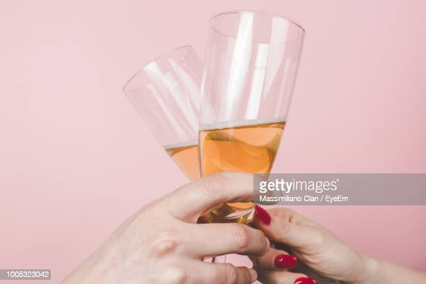 Cropped Hands Of Friends Toasting Champagne Flutes Against Pink Background