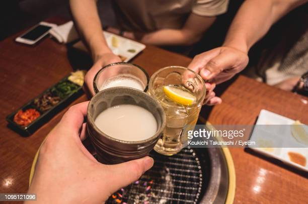 Cropped Hands Of Friends Toasting Drinks At Restaurant