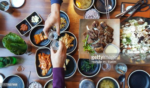 cropped hands of friends toasting drinks over food in restaurant - jeonju stock pictures, royalty-free photos & images