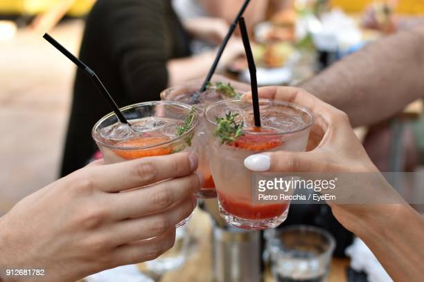 cropped hands of friends toasting drinks - cocktail party stock pictures, royalty-free photos & images