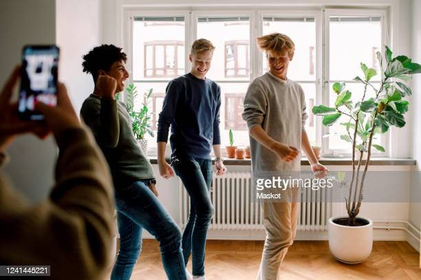 cropped hands of girl filming teenage male friends dancing in living room - facebook friends stock pictures, royalty-free photos & images
