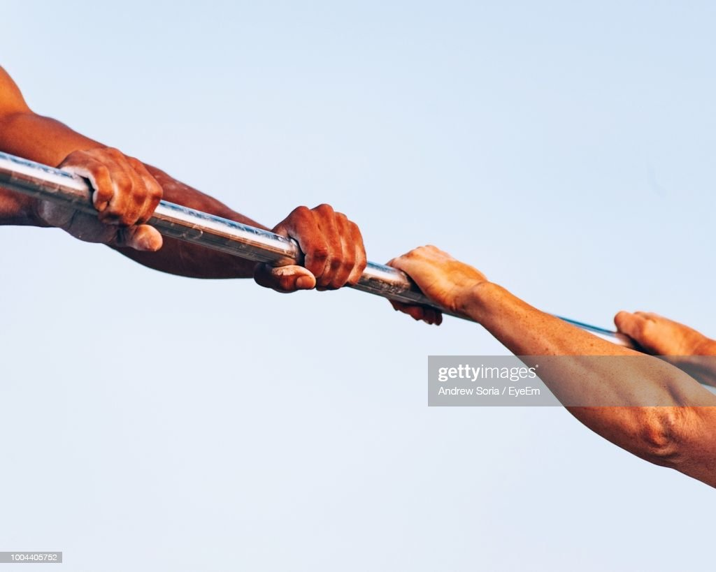 Cropped Hands Of Gymnasts Practicing On Parallel Bars Against Clear Sky : Stock Photo