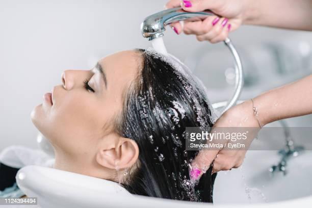 cropped hands of hairdresser washing customer hair at salon - hair colour stock pictures, royalty-free photos & images
