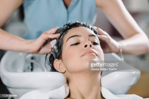 cropped hands of hairdresser washing customer hair at salon - hair treatment stock pictures, royalty-free photos & images