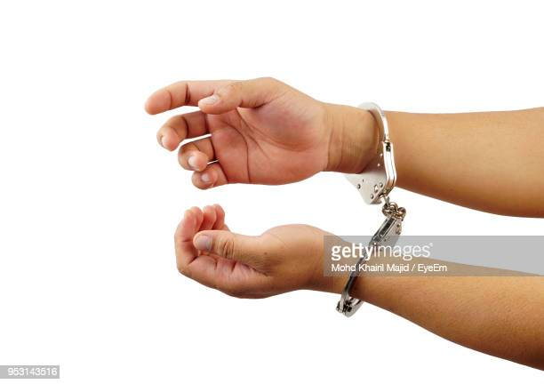 cropped hands of handcuffs over white background - handcuffs stock pictures, royalty-free photos & images