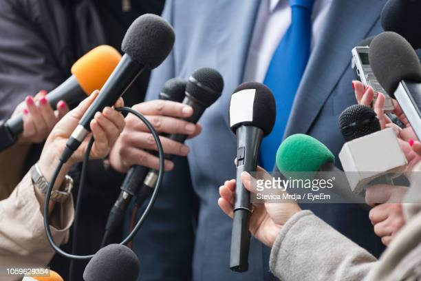 cropped hands of journalists holding microphones in front of businessman - homme politique photos et images de collection