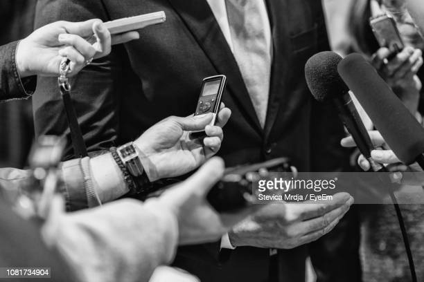 cropped hands of journalists interviewing businessman - politiek en staatsbestuur stockfoto's en -beelden