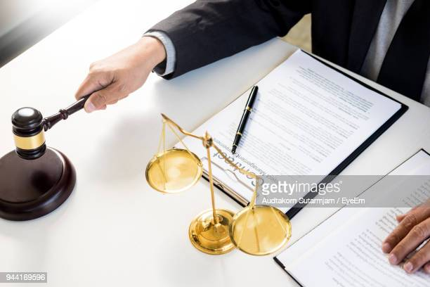 Cropped Hands Of Judge Holding Gravel At Table