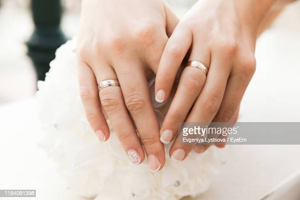 cropped hands of lesbian couple holding hands - civil partnership stock pictures, royalty-free photos & images
