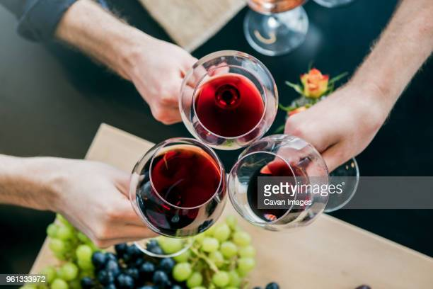 cropped hands of male friends toasting wine at tasting room - wine tasting stock pictures, royalty-free photos & images