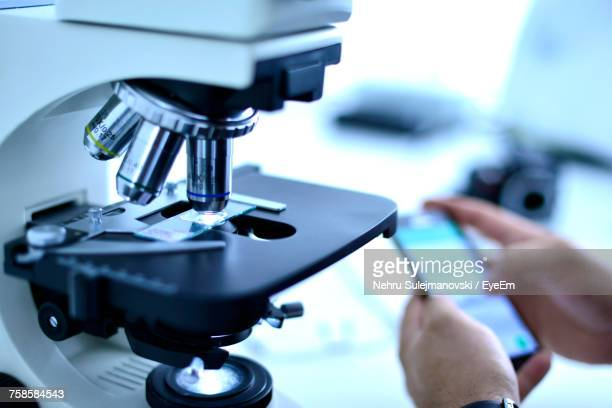 cropped hands of male scientist using mobile phone by microscope at laboratory - recherche médicale photos et images de collection